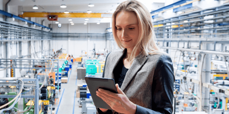 Businesswoman tracks orders on tablet device in manufacturing facility
